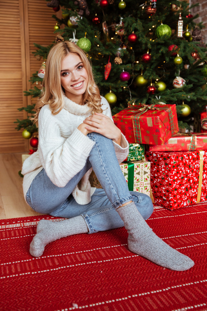 happy girl in sweater sitting on the floor near the fir tree and