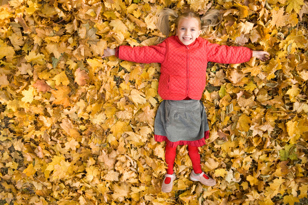 Happy girl lying on carpet of dry maple leaves and laughing