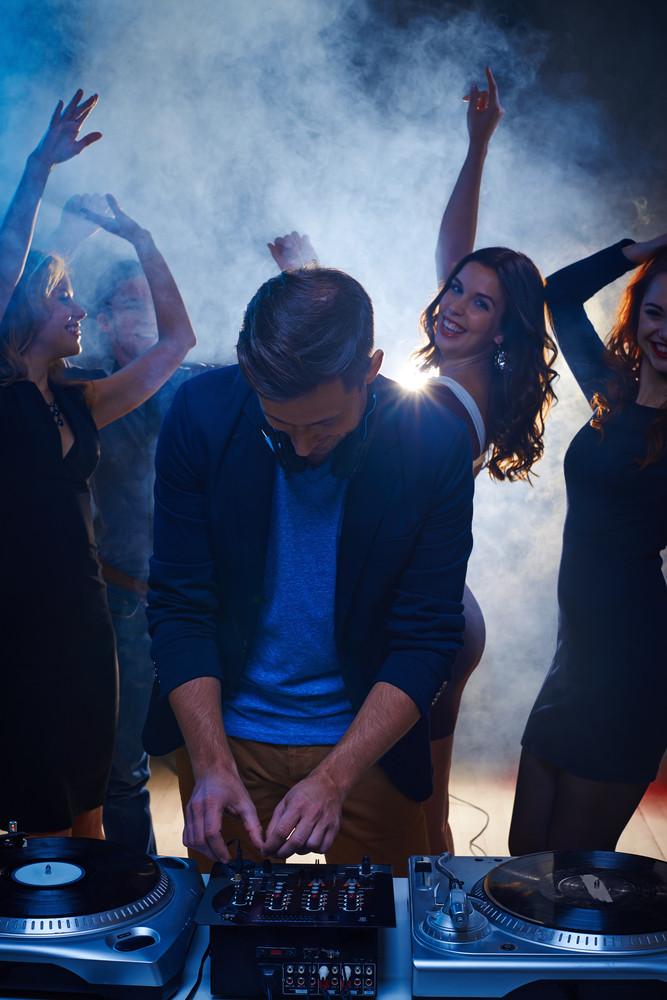 Happy girls dancing in nightclub while dj playing energetic