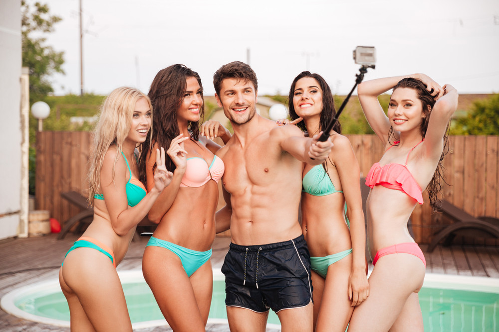 762638824653b Happy handsome young man and group of young women in swimsuits talking  selfie with smartphone in