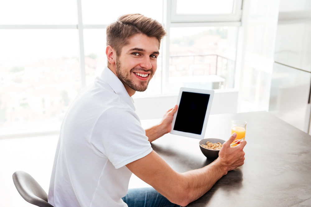 Happy handsome young man having breakfast and using blank screen tablet at home