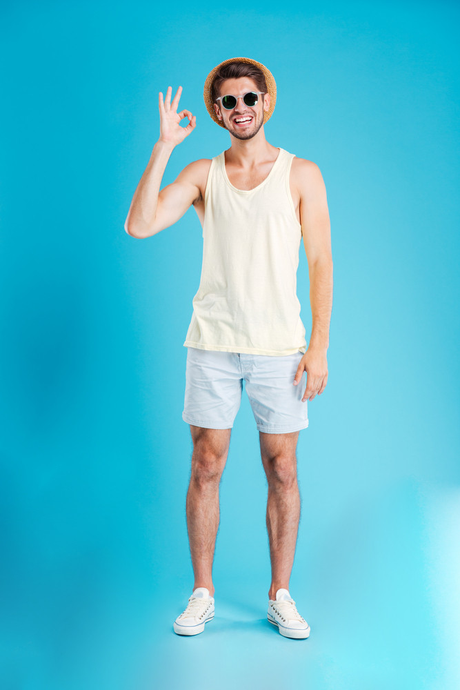 Happy handsome young man in hat and sunglasses standing and showing ok sign over blue background