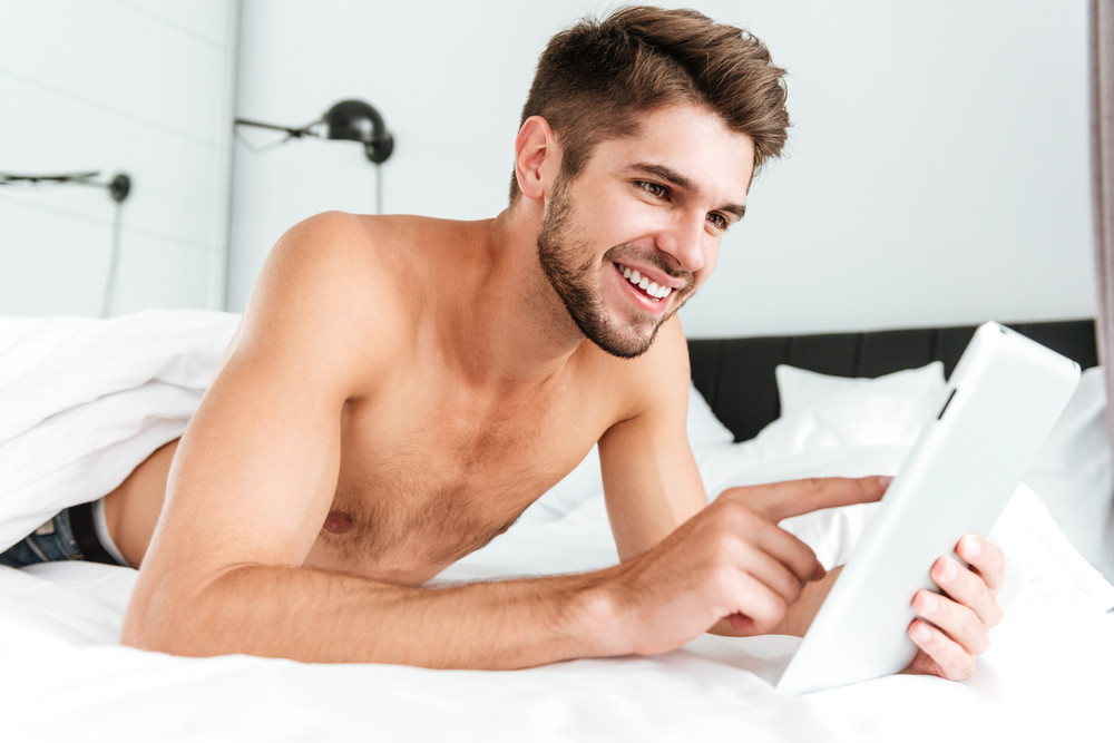 Happy handsome young man smiling and using tablet in bed