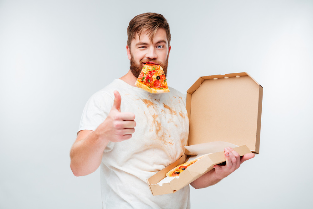 Happy hungry man eating pizza and showing thumbs up gesture isolated on white background