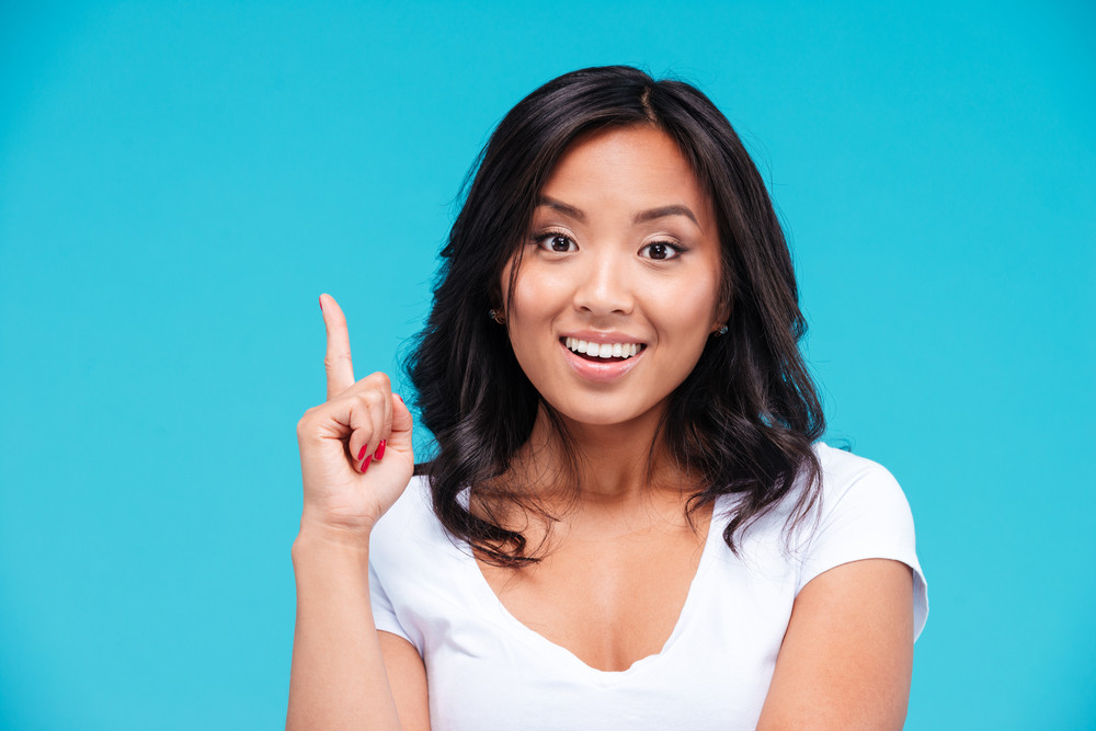 Happy inspired young vietnamese woman pointing up and having an idea over blue background