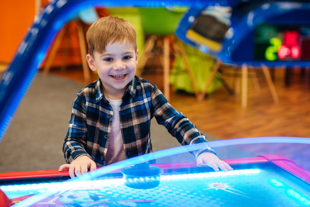 Happy little boy playing air hockey at indoor playground