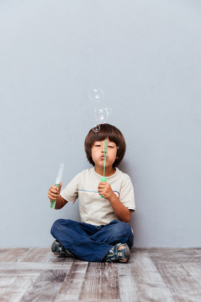 Happy little boy sitting and blowing soap bubbles over gray background
