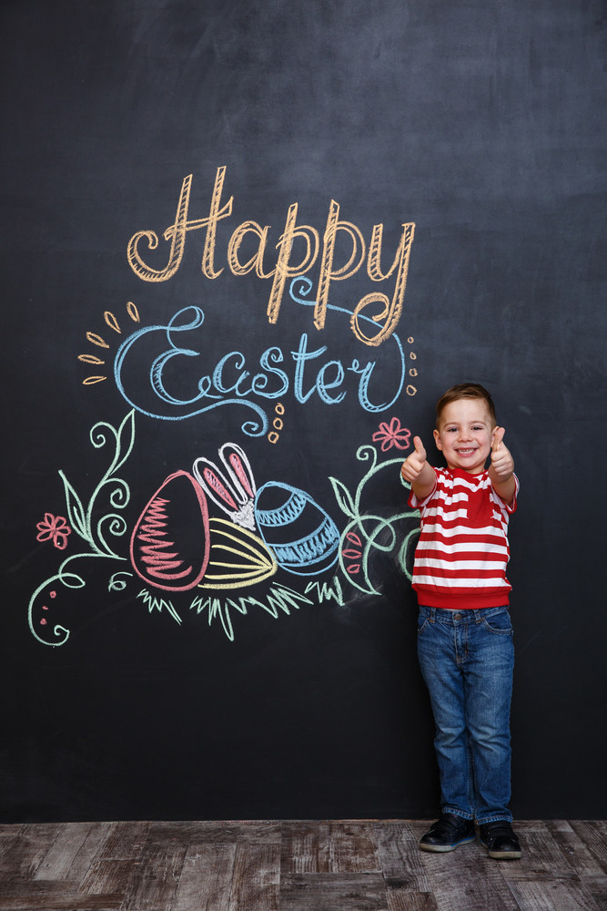 Happy little boy standing and showing two thumbs up over chalk board with easter doodles background