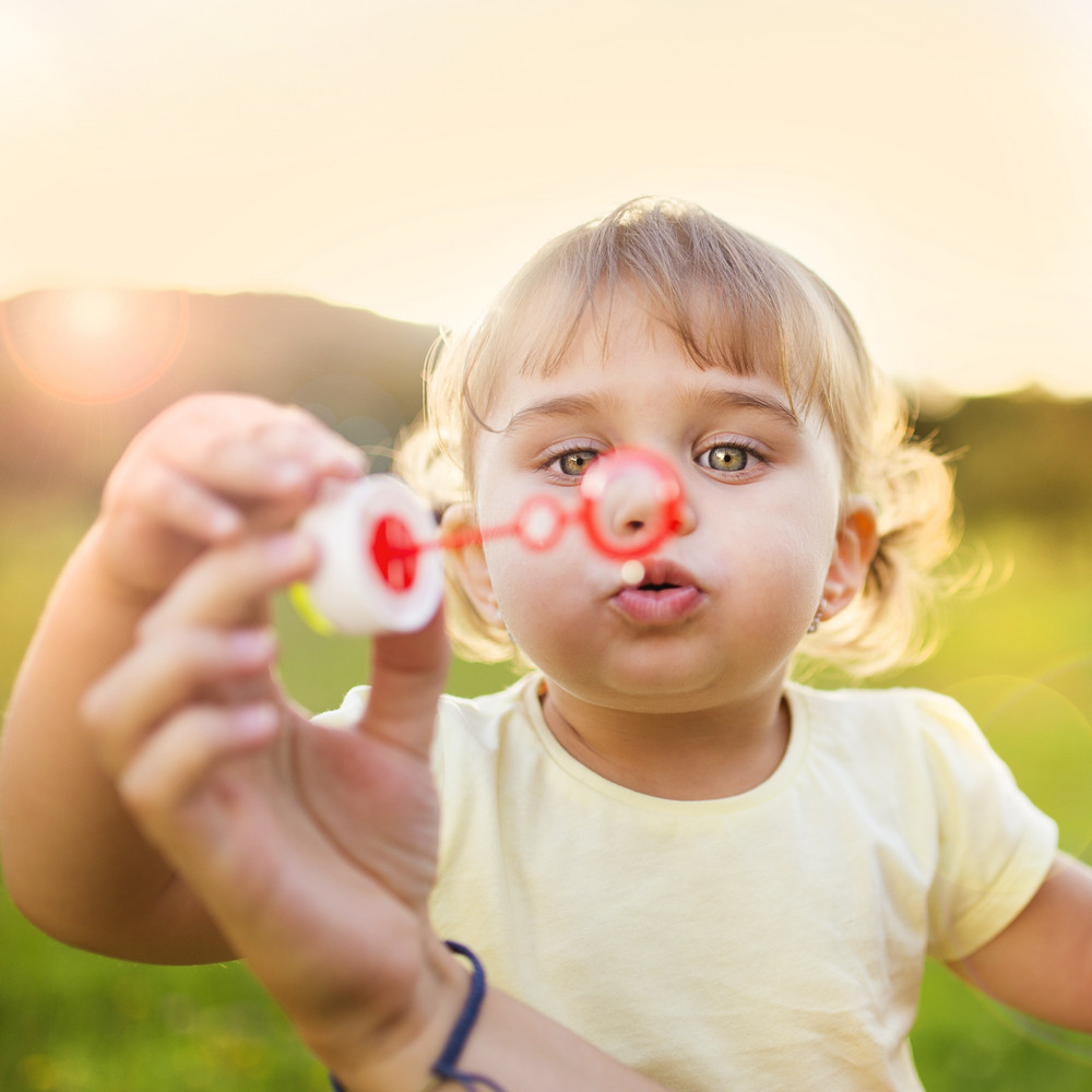 Happy little girl blowing bubbles in summer nature