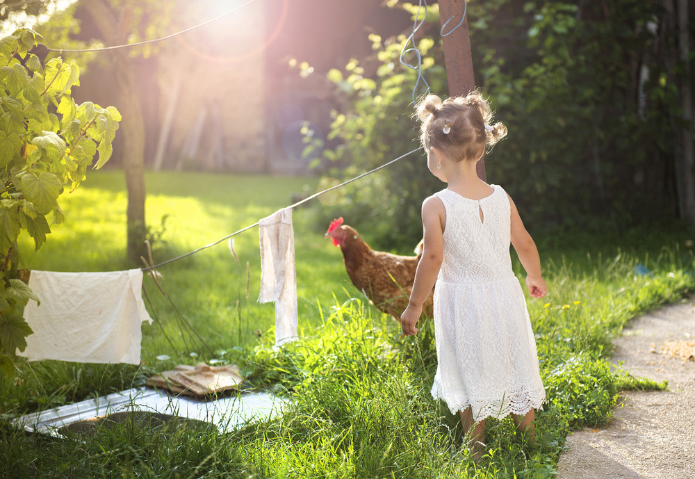 Happy little girl having fun in garden near the old farmhouse