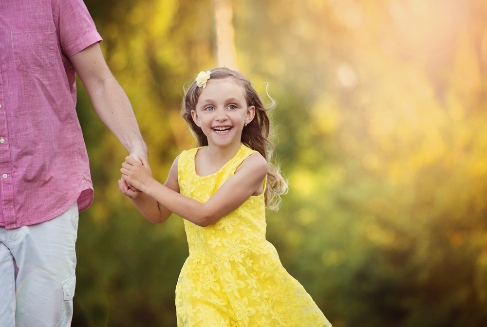 Happy little girl holding dad's hand and walking in the park