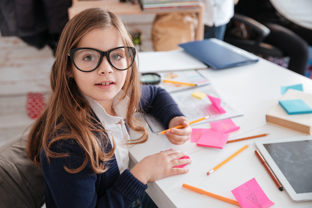 Happy little girl in glasses sitting and writing at the table