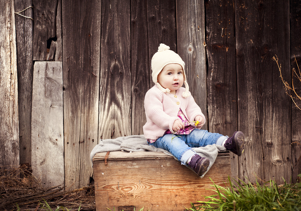 Happy little girl in warm clothes is sitting in front of the fence in autumn nature