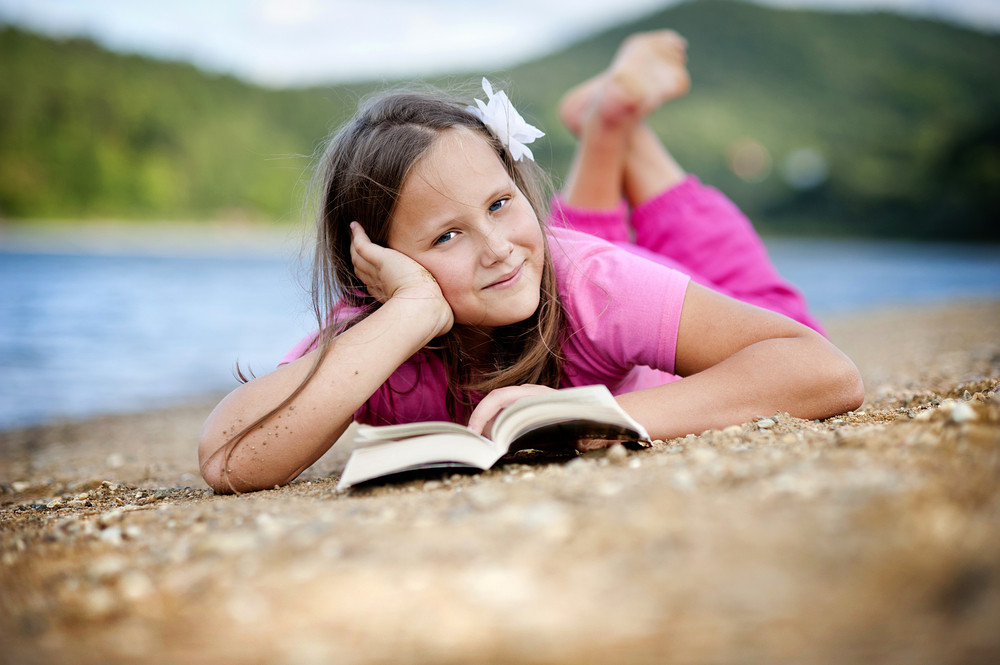 Happy little girl is reading book by the lake