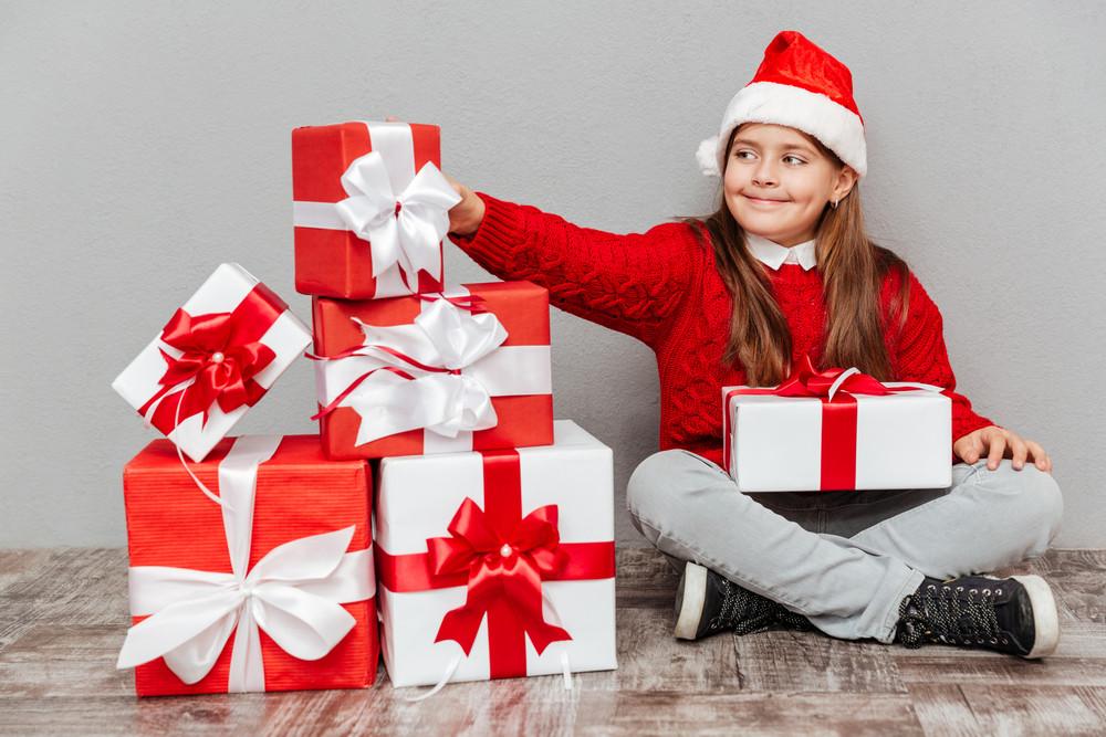 Happy lovely little girl in santa claus hat taking present box