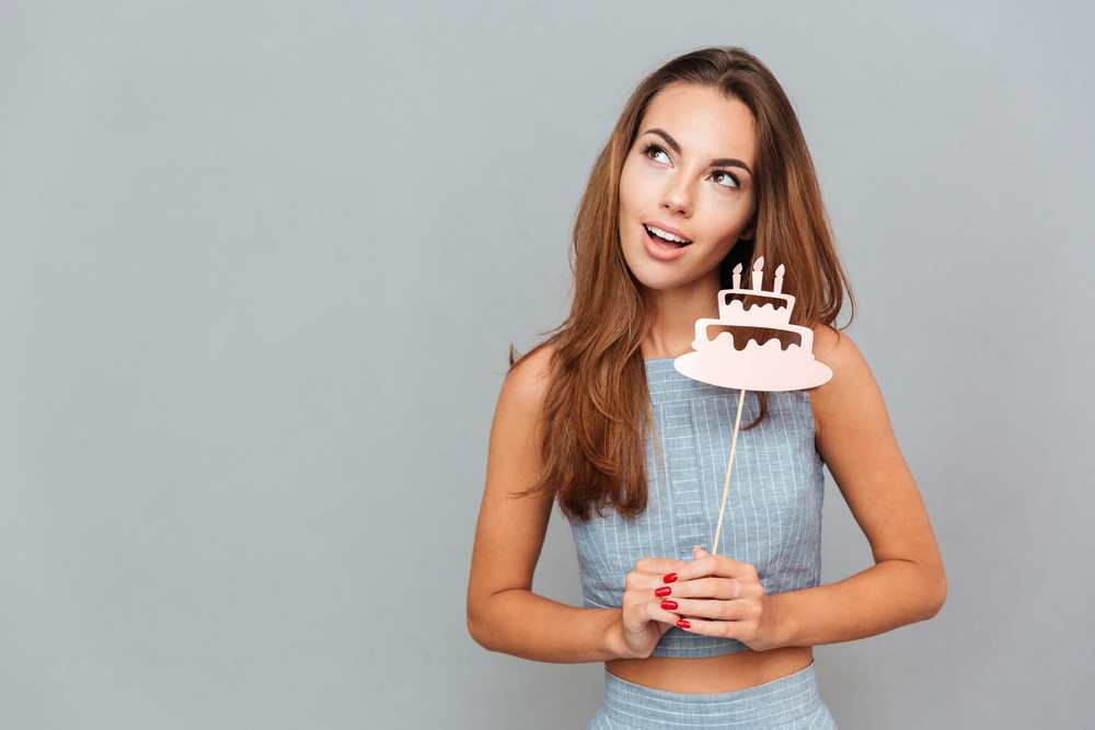 Happy lovely young woman holding birthday cake props over grey background