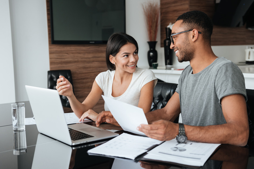 Happy loving young couple using laptop and analyzing their finances with documents. Look at each other.