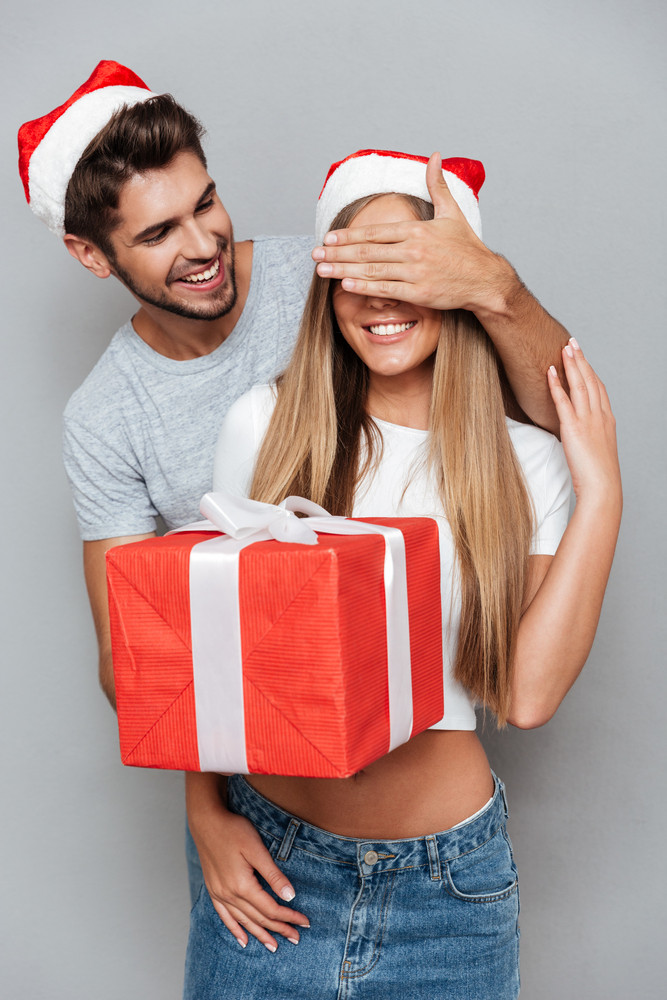 Happy man covers with hand eyes of his girlfriend. man gives a gift. gray background