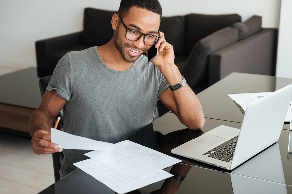 Happy man dressed in grey t-shirt and wearing eyeglasses talking on cellphone while looking on documents.