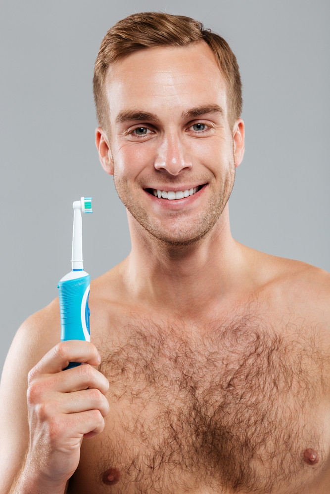 Happy man holding toothbrush and looking at camera isolated on the gray background