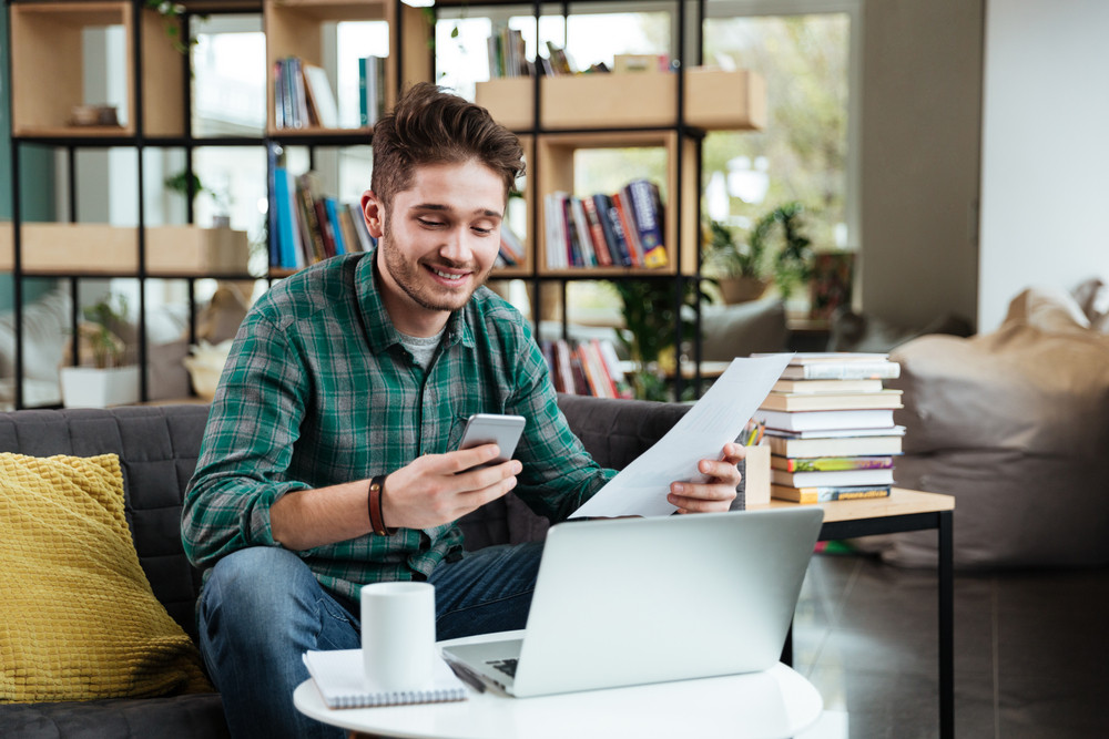 Happy man in green shirt with documents looking at phone and sitting on sofa by the table with laptop. Coworking