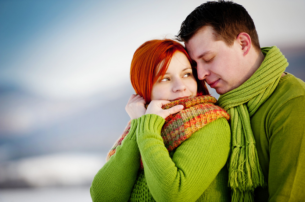 Happy man in love with his pregnant woman outside in winter scenery.