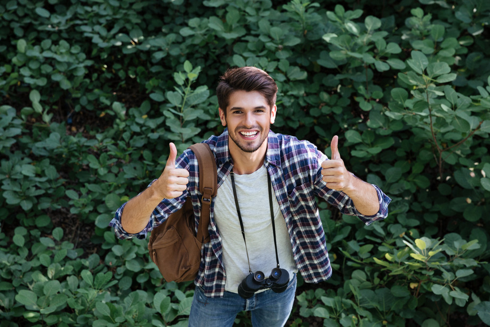 Happy man in shirt with binoculars and backpack in forest shows fingers up. looking at camera. top view