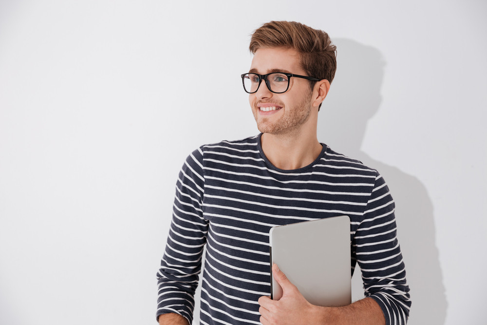Happy Man in striped sweater holding laptop in hand and looking away. Isolated gray background