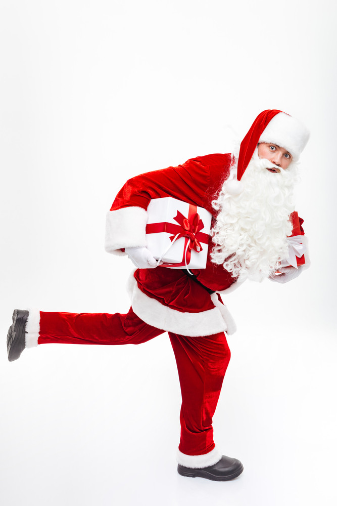 Happy man santa claus holding present boxes and running