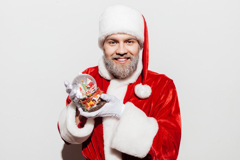 Happy man santa claus smiling and holding snowball