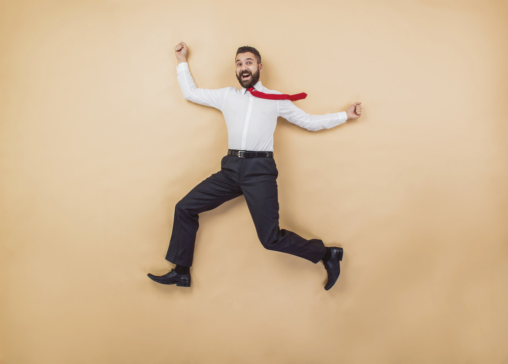 Happy manager jumping high in a victorious pose. Studio shot on a beige background.
