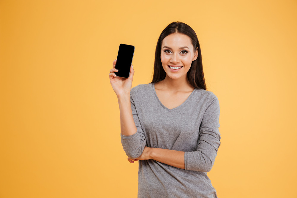 Happy model with phone in studio looking at camera. isolated orange background