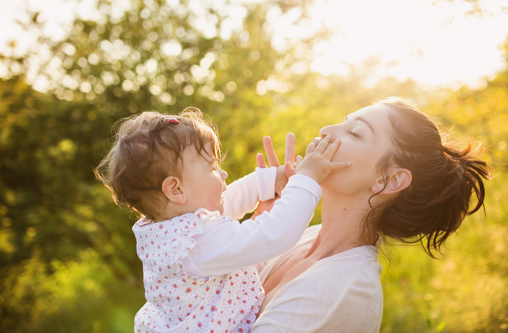 Happy mother and her baby having fun outside in spring nature