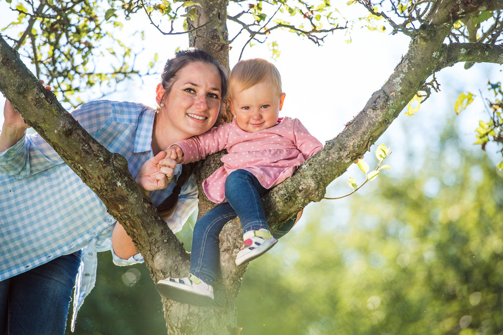 Happy mother and her daughter having fun outside in spring nature