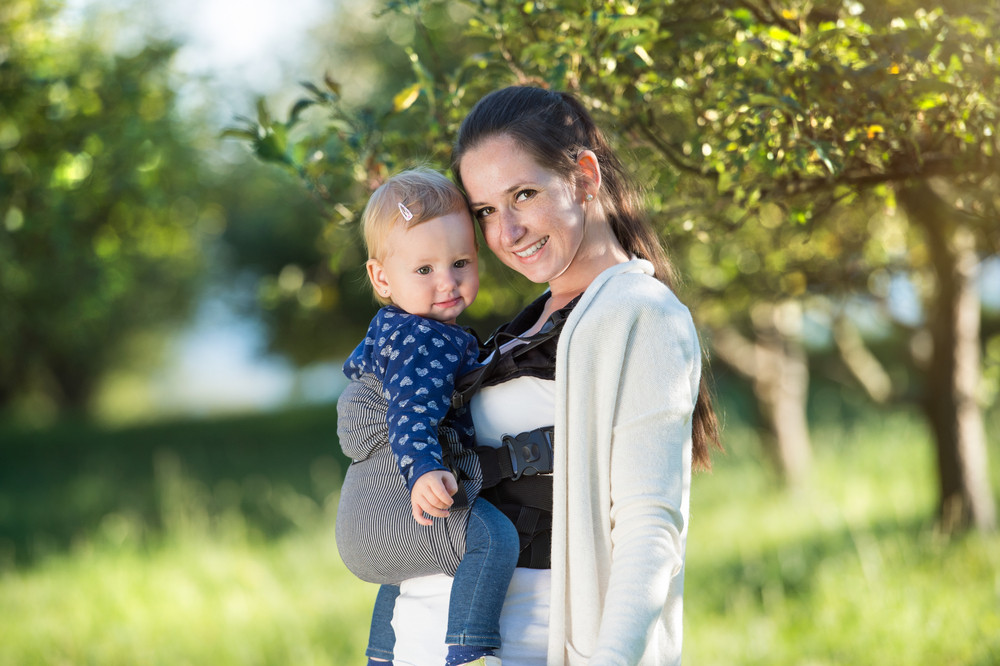 Happy mother and her daughter outside in spring nature