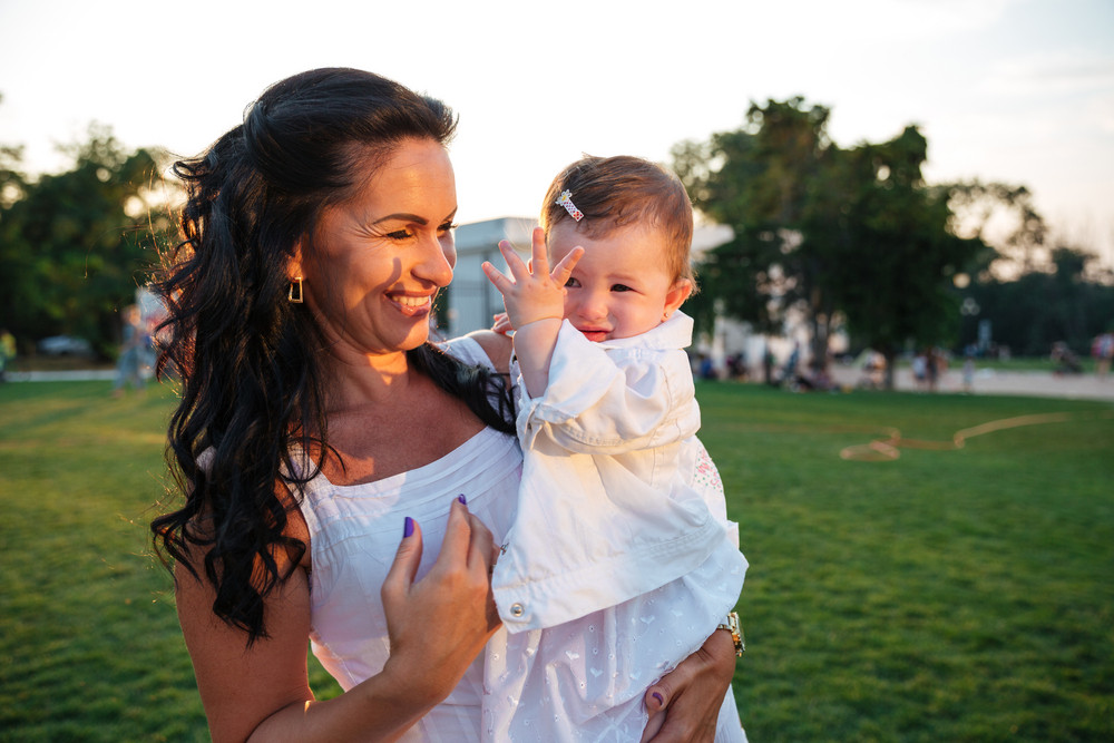 Happy mother holding her little daughter and laughing in park