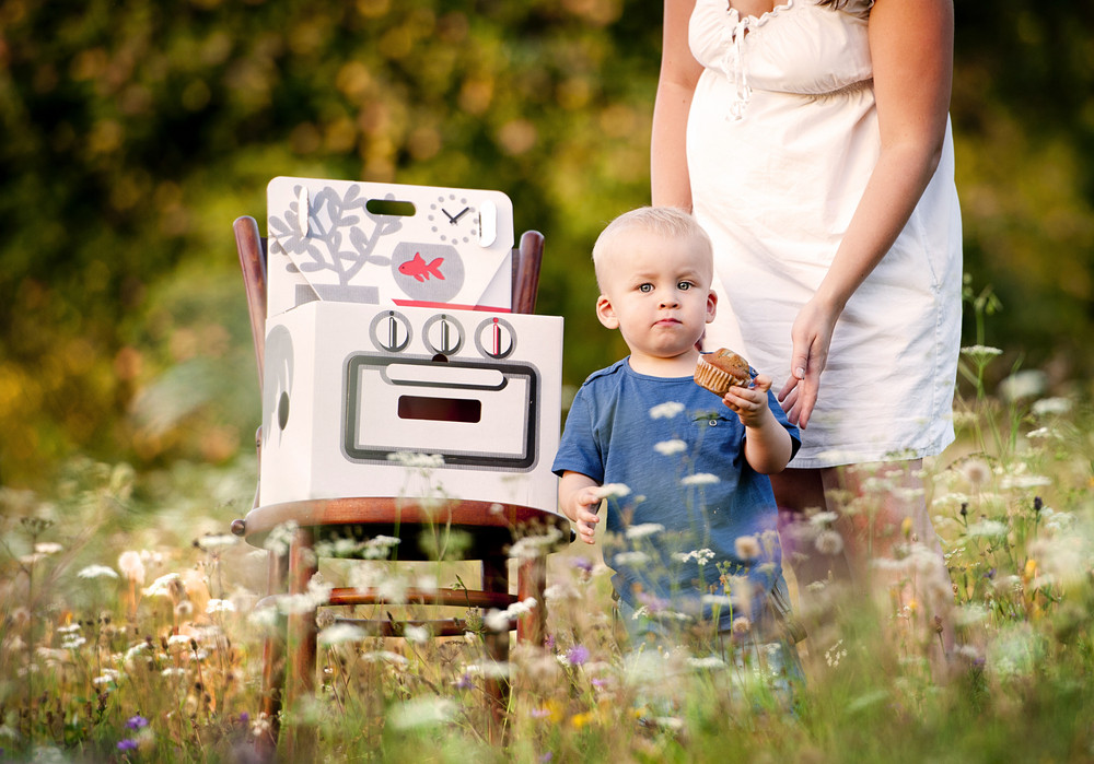 Happy mother playing with her little son in the meadow with toy oven