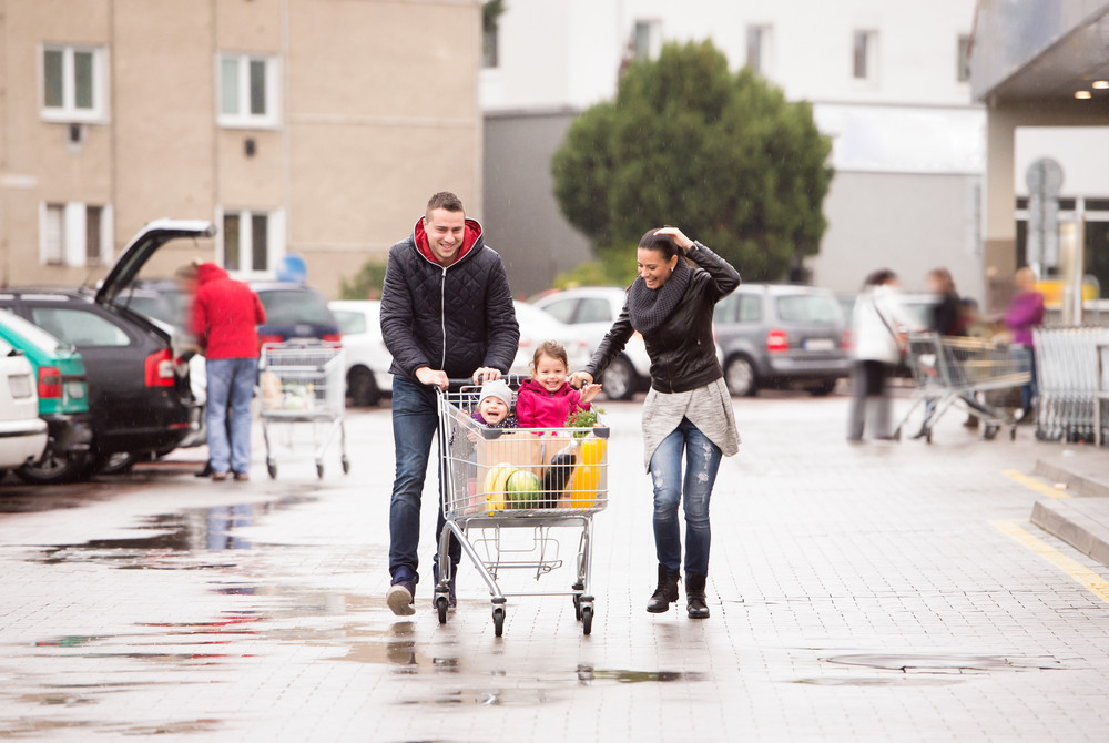 Happy parents pushing shopping cart with groceries and their two little daughters in front of supermarket after buying food. Autumn rainy day.
