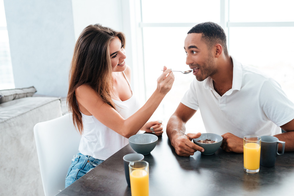 Happy playful young couple having breakfast together on the kitchen