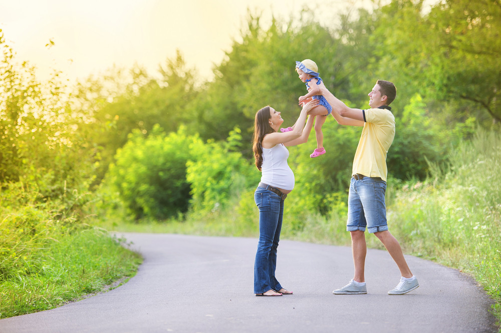 Happy pregnant family having fun during the walk in summer nature