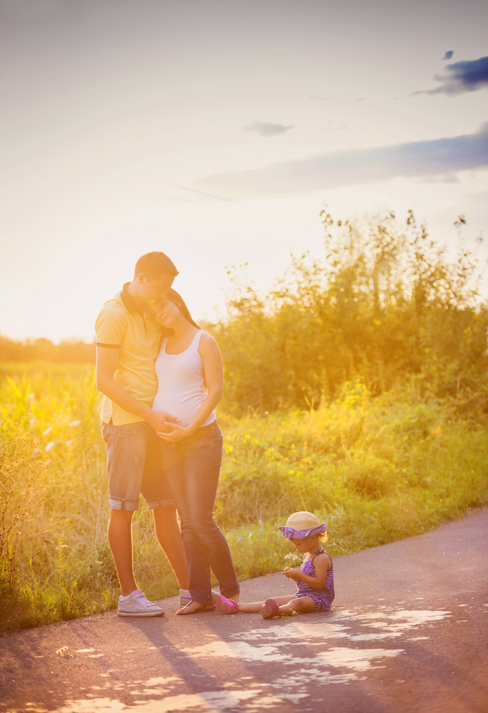 Happy pregnant family with little daughter spending time together in summer nature