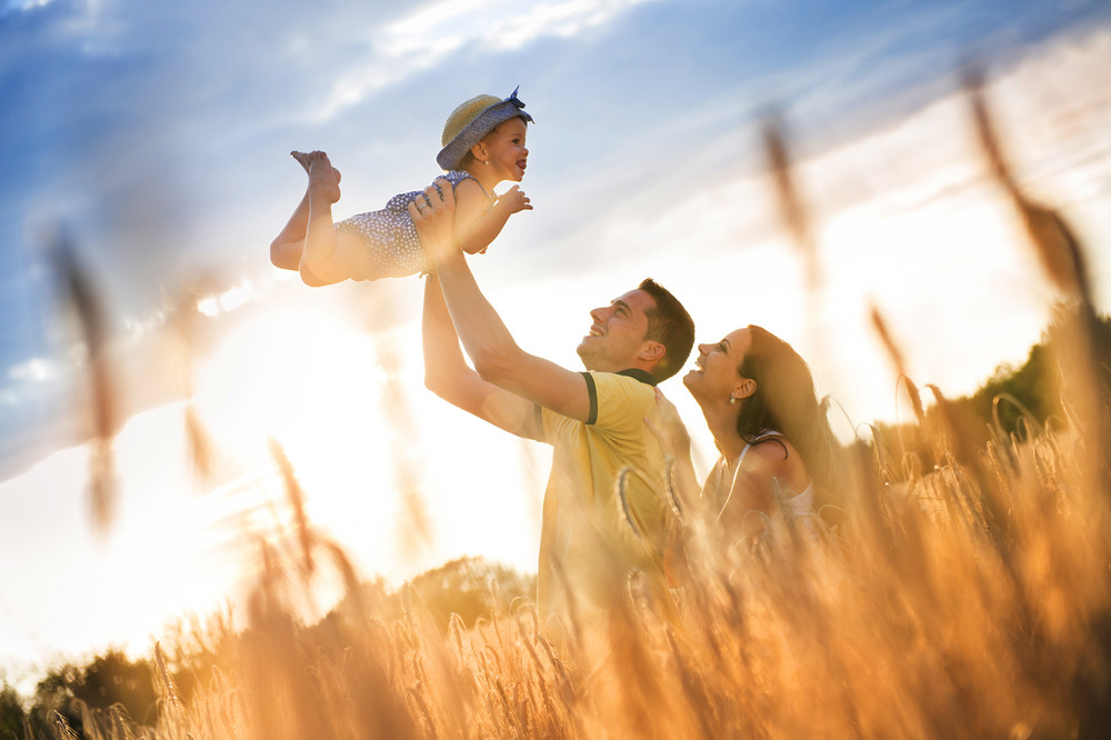 Happy pregnant family with little daughter spending time together in sunny field