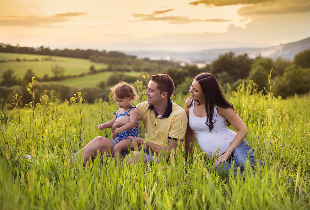 Happy pregnant family with little daughter spending time together sitting in grass in summer nature