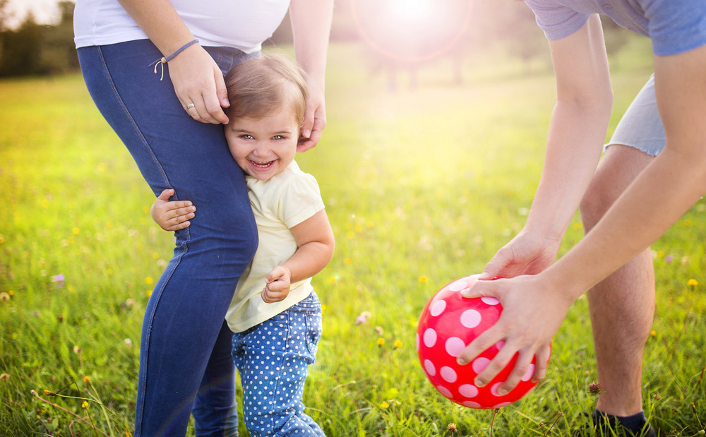 Happy pregnant family with little girl having fun playing with ball in summer nature