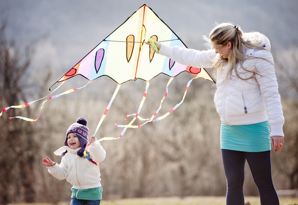 Happy pregnant mother with her little daughter are having fun with kite in autumn nature