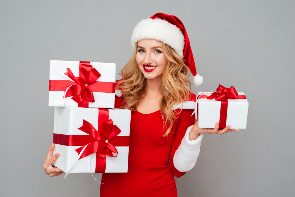 Happy pretty woman in red santa claus dress and hat holding stack of gift boxes isolated on the gray background
