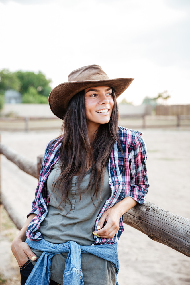 Happy pretty young woman cowgirl standing near the fence