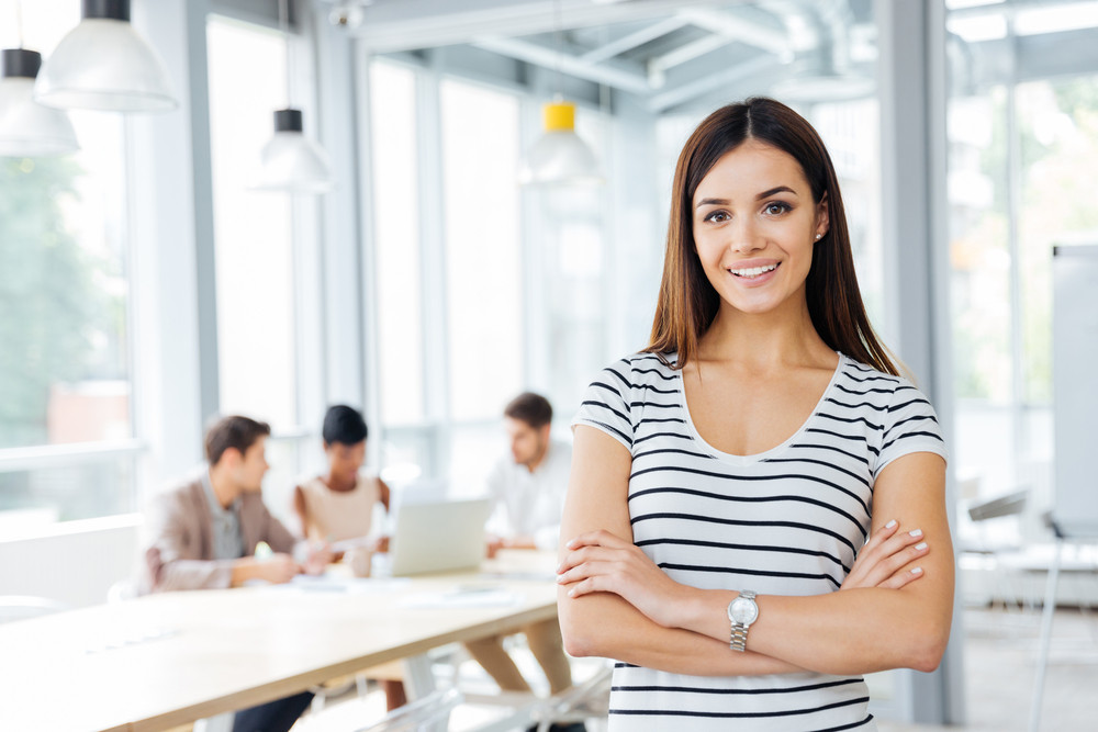 Happy pretty young woman standing with arms crossed in office