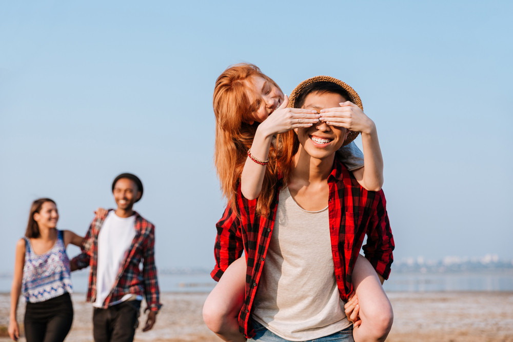 Happy redhead young woman covered eyes of her boyfriend by hands outdoors