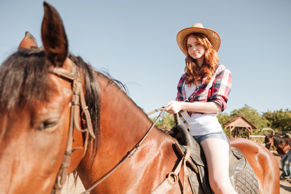 Happy redhead young woman cowgirl smiling and riding horse at ranch